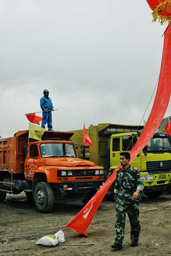 soldado chino que camina más allá en algunos camiones resistentes con un trabajador en el top que agita la bandera roja nacional imagen de archivo