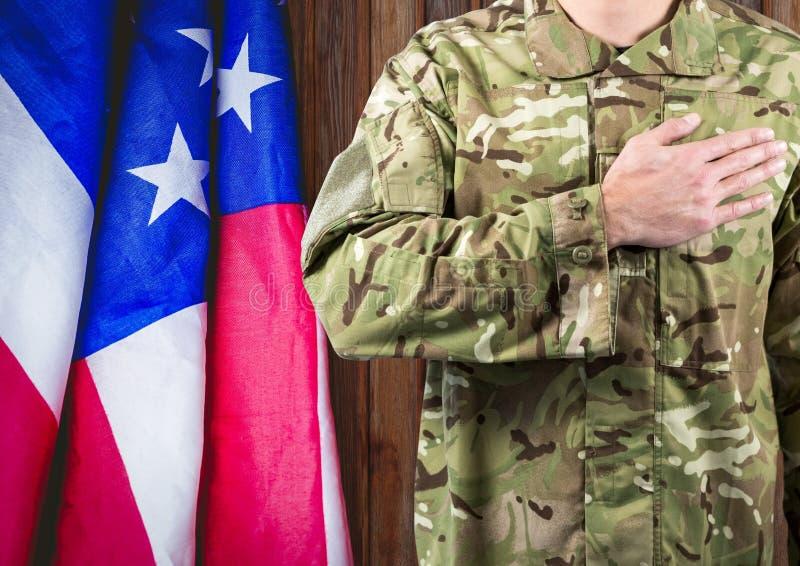 soldado com a mão na lareira e na bandeira dos EUA atrás foto de stock