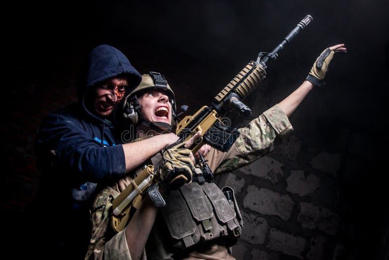 Soldado con el arma atacado por el zombi fotografía de archivo