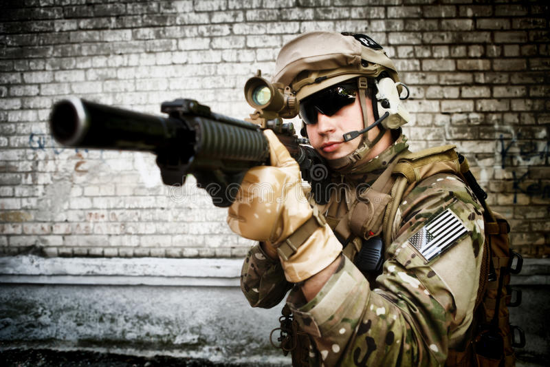 Soldado con un rifle contra la pared imagen de archivo libre de regalías