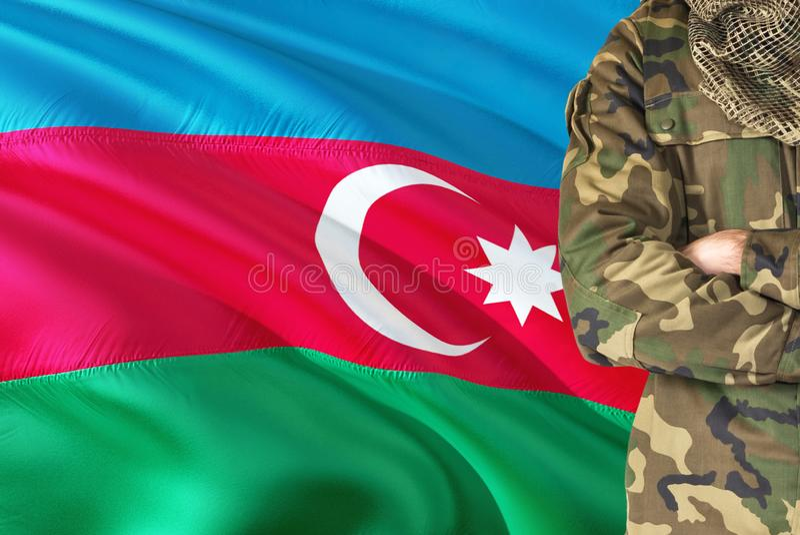 Soldado cruzado de las armas con la bandera que agita nacional en el fondo - tema militar de Azerbaijan imagenes de archivo