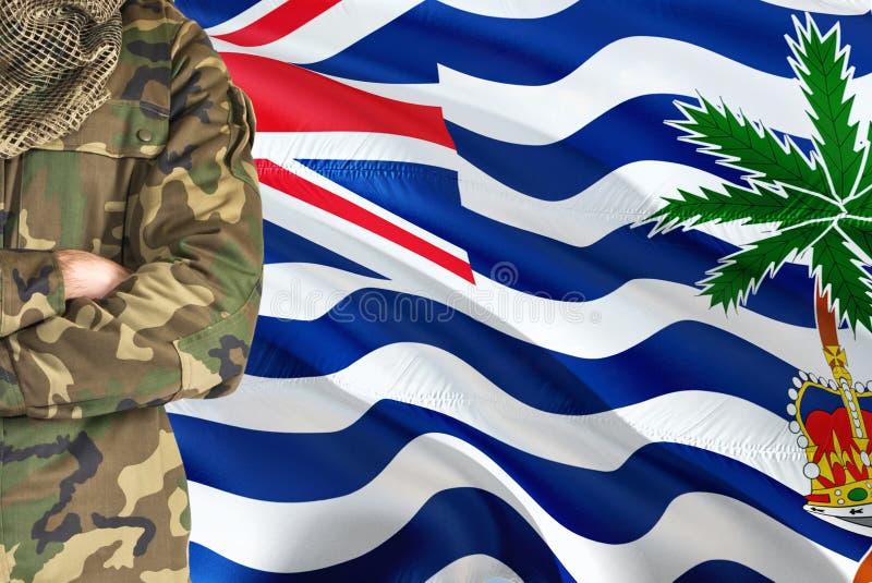 Soldado cruzado de las armas con la bandera que agita nacional en el fondo - tema militar del territorio del Océano Índico britán imagenes de archivo