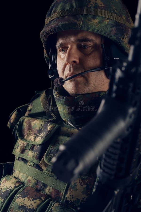 Soldado das forças especiais com o rifle no fundo escuro imagens de stock royalty free