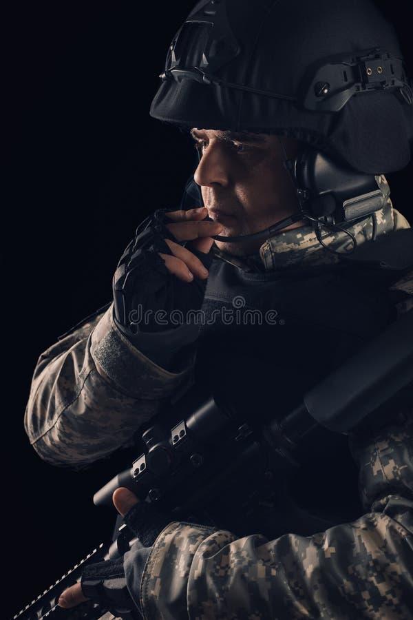 Soldado das forças especiais com o rifle no fundo escuro imagens de stock
