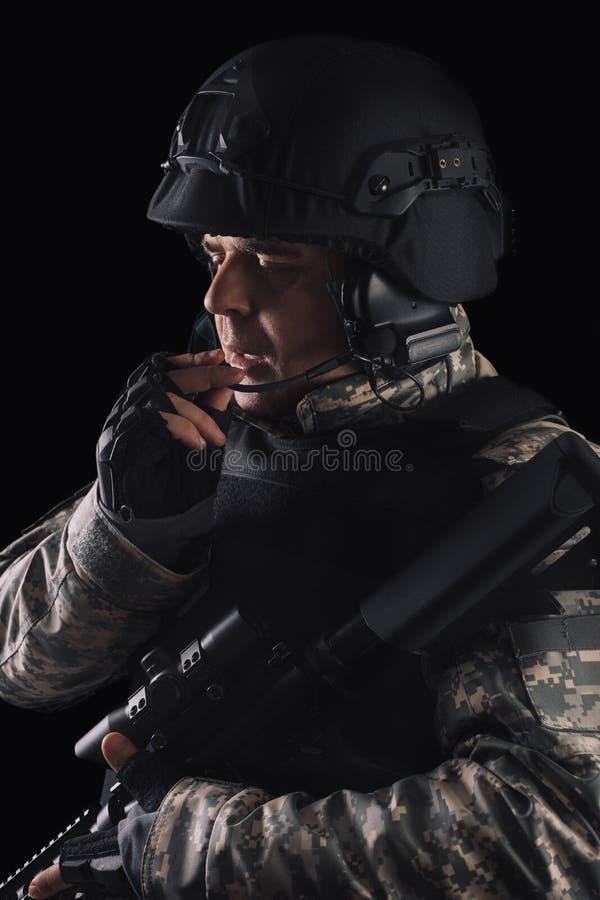Soldado das forças especiais com o rifle no fundo escuro imagem de stock