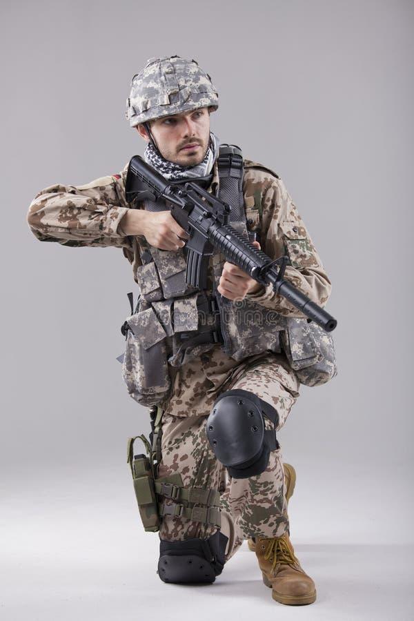 Soldado de arrodillamiento con la ametralladora fotografía de archivo