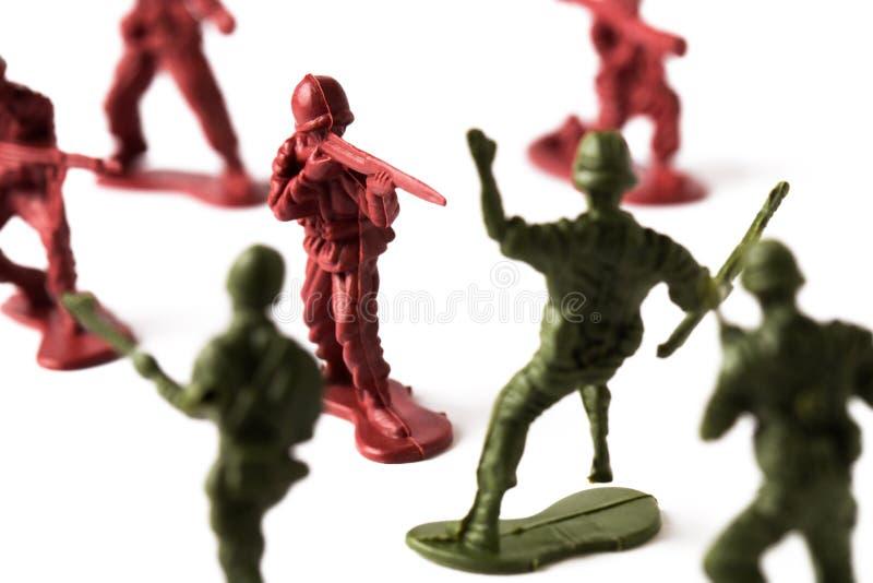 Soldado de brinquedo que dispara em um inimigo, isolado no fundo branco imagens de stock