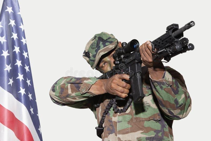 Soldado de los E.E.U.U. Marine Corps que apunta el rifle de asalto M4 con la bandera americana contra fondo gris foto de archivo