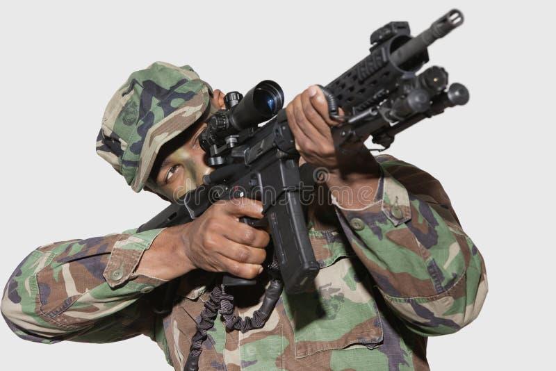Soldado de los E.E.U.U. Marine Corps que apunta el rifle de asalto M4 contra fondo gris imagen de archivo libre de regalías