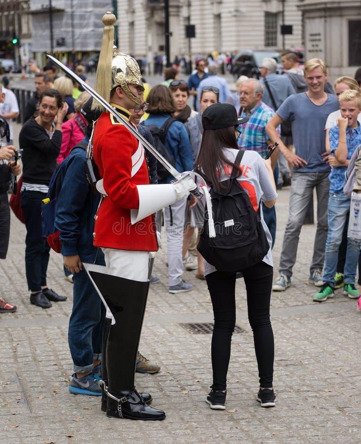Soldado de los guardias de caballo reales en Londres, rodeado por los turistas que toman las fotos imagenes de archivo