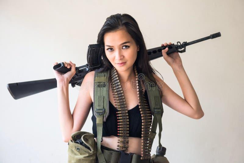Soldado de sexo femenino con el arma del rifle M16 imagenes de archivo