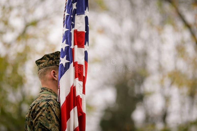 Soldado del Ejército de los EE. UU. con la bandera de los E.E.U.U. imagenes de archivo