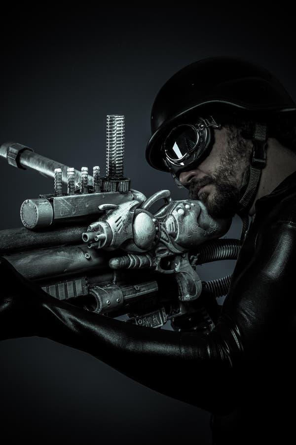 Soldado del futuro con el arma enorme y el cañón del laser, señalando imagenes de archivo