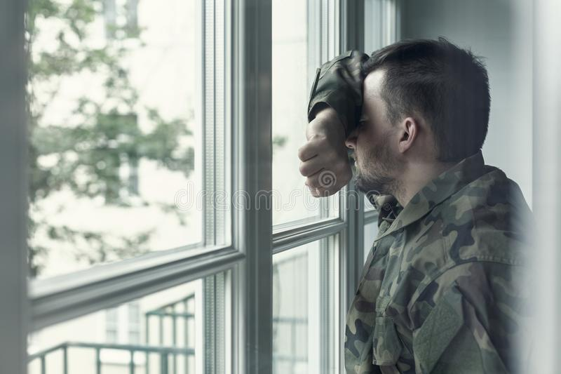 Soldado deprimido e triste no uniforme verde com traumatismo após a guerra que está perto da janela imagens de stock