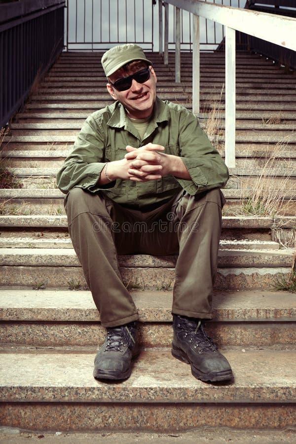 Soldado divertido en las escaleras del edificio fotografía de archivo