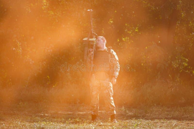 Soldado do destacamento do objetivo especial com uma metralhadora em suas mãos que estão no campo de batalha no fumo alaranjado imagens de stock royalty free