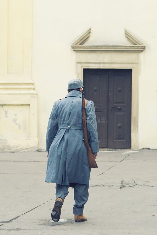 Soldado do exército austro-Hungarian com um rifle em seu ombro que anda em uma porta fechado da igreja católica romana s Unif do  fotos de stock royalty free