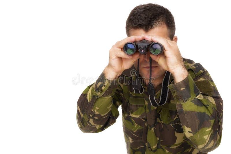 Soldado do exército que olha através dos binóculos fotografia de stock