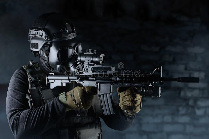 Soldado do guerreiro na máscara e no rifle de gás que visam a noite fotos de stock royalty free