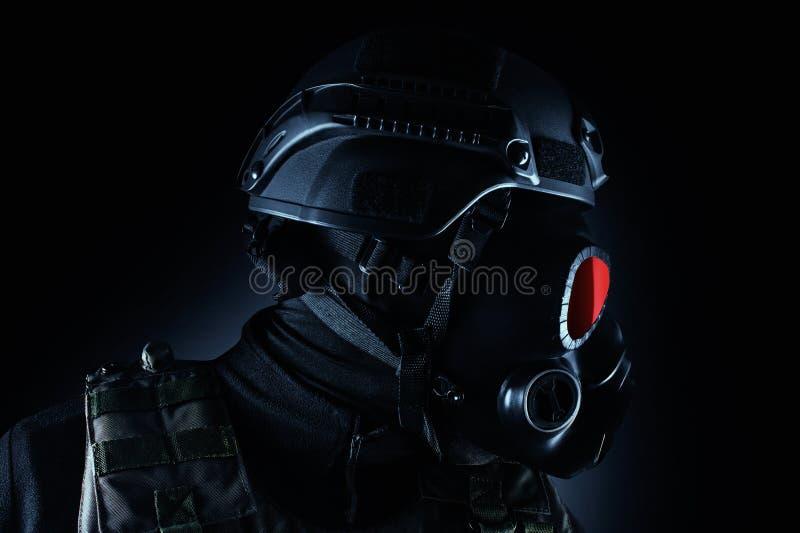 Soldado do guerreiro no close up da opinião do perfil da posição da máscara e do rifle de gás imagens de stock