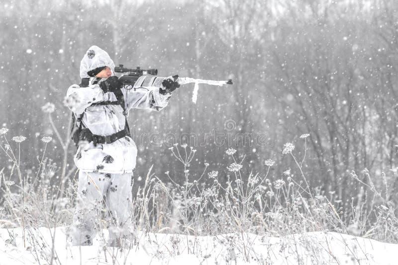Soldado do homem no inverno em uma caça com um rifle de atirador furtivo na camuflagem branca do inverno que aponta a posição na  imagens de stock royalty free