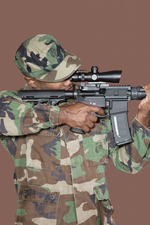 Soldado dos E.U. Marine Corps do homem que aponta a espingarda de assalto M4 sobre o fundo marrom foto de stock royalty free