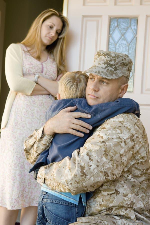 Soldado Embracing Son Before que parte quando mãe que olha os imagens de stock