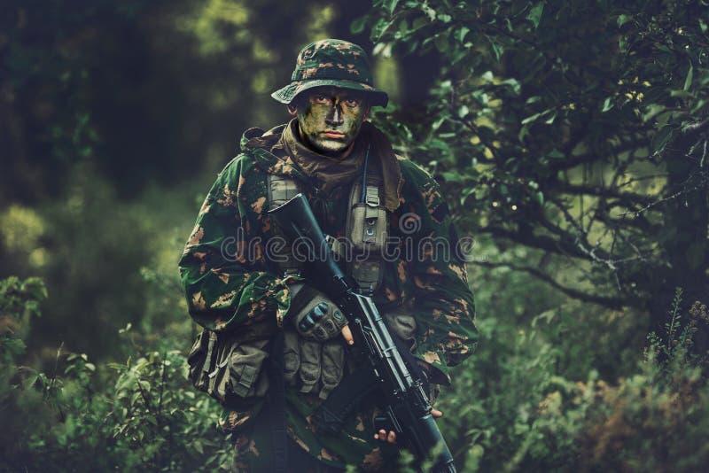 Soldado en área del bosque en el crepúsculo imagenes de archivo