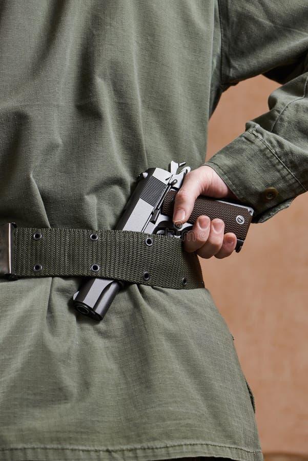 Soldado en arma que se sostiene uniforme en su correa foto de archivo libre de regalías