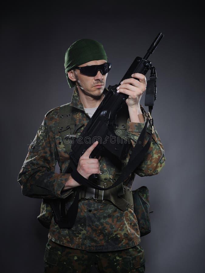 Soldado en camuflaje y munición con un rifle fotos de archivo