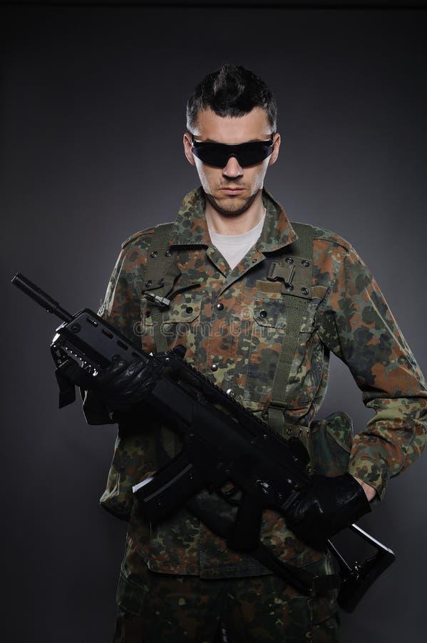 Soldado en camuflaje y munición con un rifle imagenes de archivo