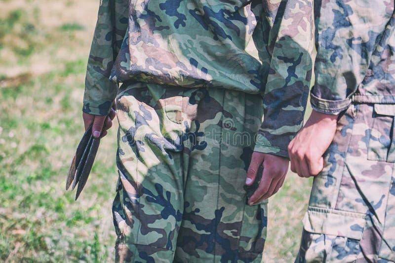 Soldado en el camuflaje que sostiene los cuchillos que lanzan foto de archivo libre de regalías