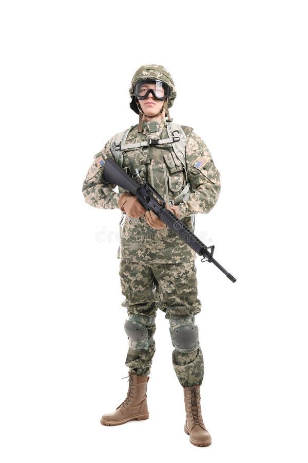 Soldado en el camuflaje que sostiene el rifle en fondo fotografía de archivo