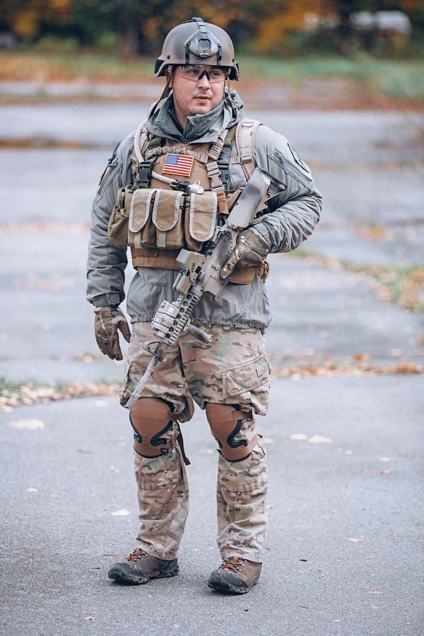 Soldado en engranaje protector con un rifle en sus manos imagen de archivo