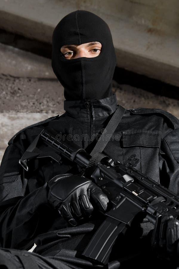 Soldado en uniforme negro con un arma imagen de archivo