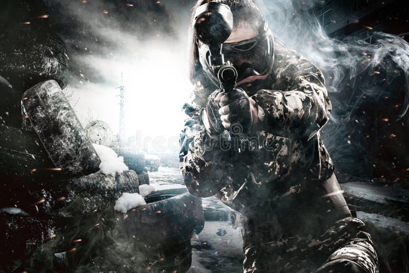 Soldado enmascarado pesadamente armado de Paintball en fondo apocalíptico de los posts Concepto del anuncio fotos de archivo libres de regalías