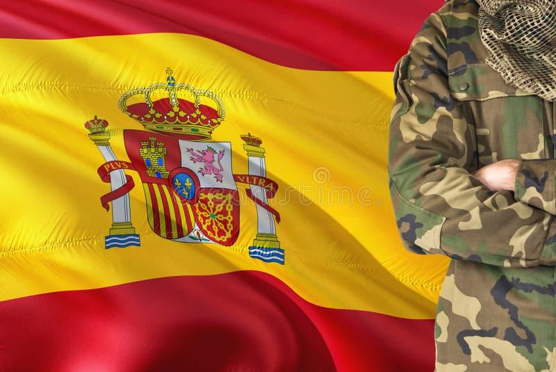 Soldado español cruzado de las armas con la bandera que agita nacional en el fondo - tema militar de España foto de archivo