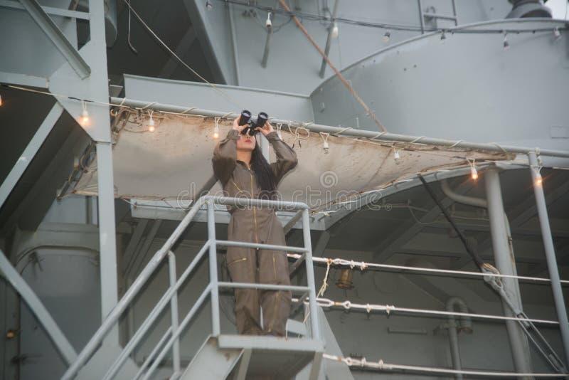 Soldado fêmea asiático bonito que olha com binóculos fotografia de stock