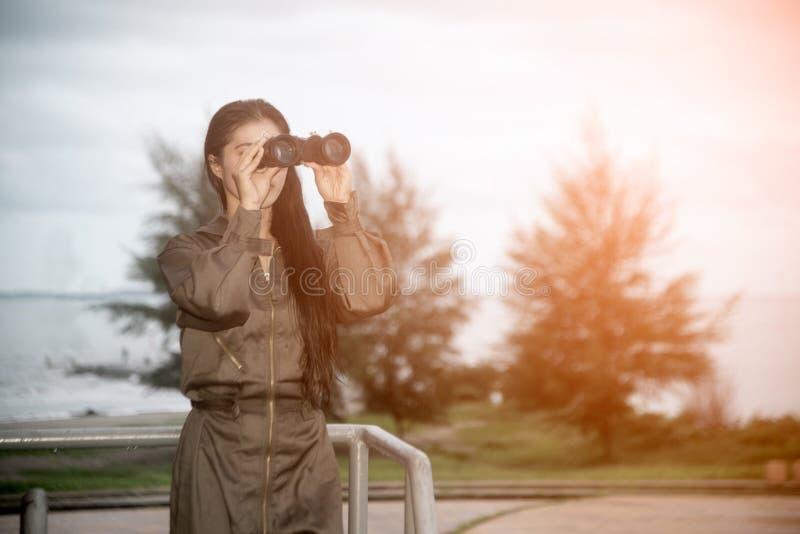 Soldado fêmea asiático bonito que olha com binóculos foto de stock