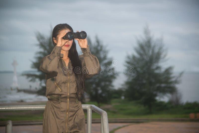 Soldado fêmea asiático bonito que olha com binóculos fotos de stock royalty free