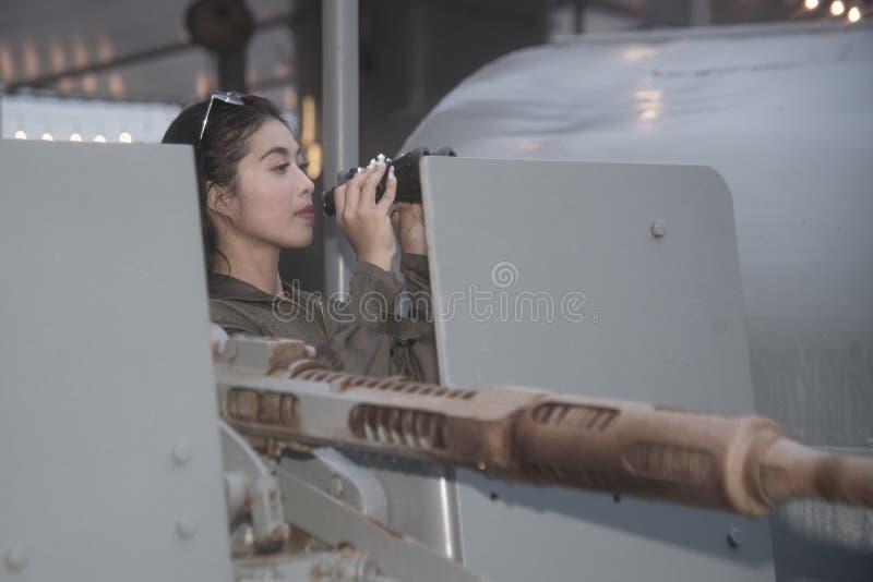 Soldado fêmea asiático bonito que olha com binóculos foto de stock royalty free