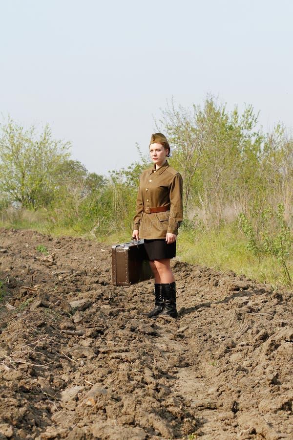 Soldado fêmea soviético com mala de viagem e no uniforme da segunda guerra mundial que está em uma estrada arada foto de stock royalty free