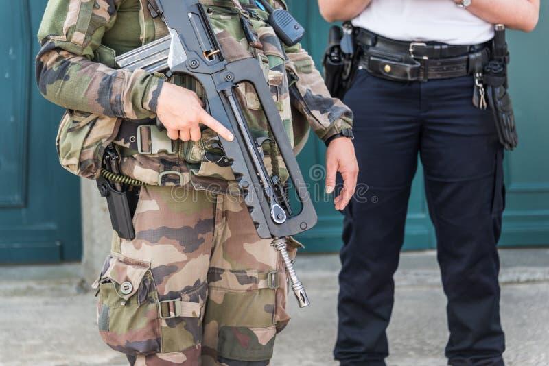 Soldado francés con un rápido automático, policía en el concepto de estado del fondo, de la seguridad y de la emergencia foto de archivo