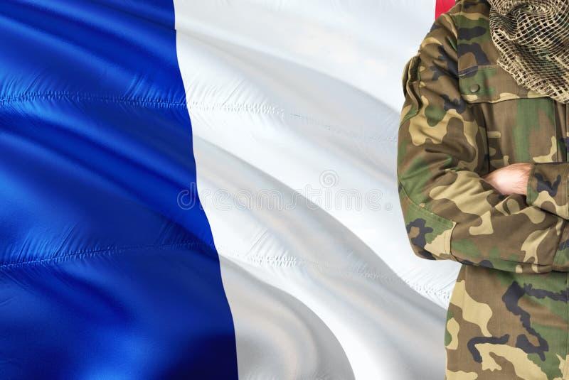 Soldado francês cruzado dos braços com a bandeira de ondulação nacional no fundo - tema militar de França fotos de stock royalty free