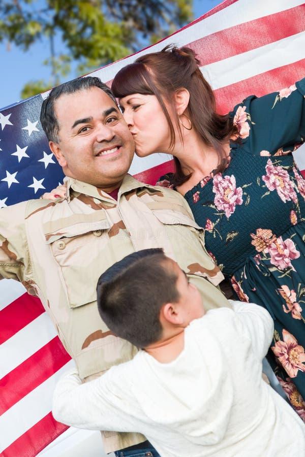 Soldado hispánico de sexo masculino Celebrating His Return de las fuerzas armadas que sostiene la bandera americana foto de archivo