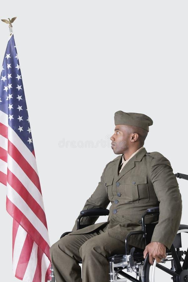 Soldado joven de los E.E.U.U. en la silla de ruedas que mira la bandera americana sobre fondo gris imágenes de archivo libres de regalías