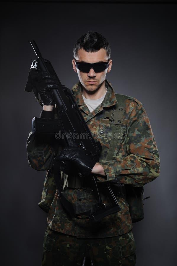 Soldado joven en camuflaje con un arma. foto de archivo