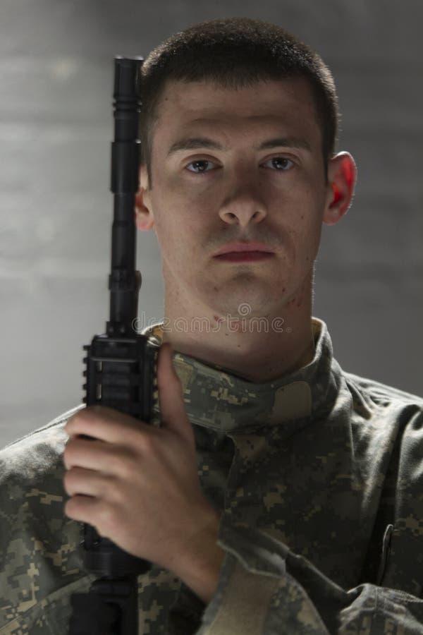 Soldado joven que sostiene el rifle de asalto, vertical fotografía de archivo