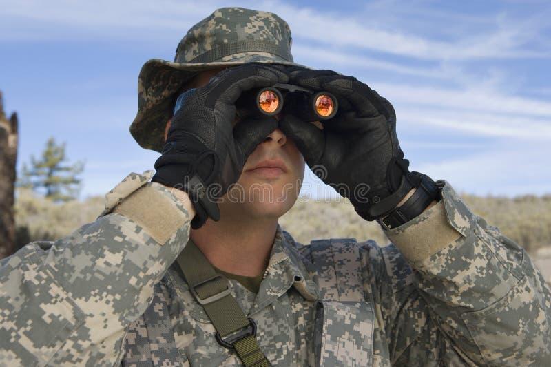 Soldado Looking Through Binoculars foto de stock