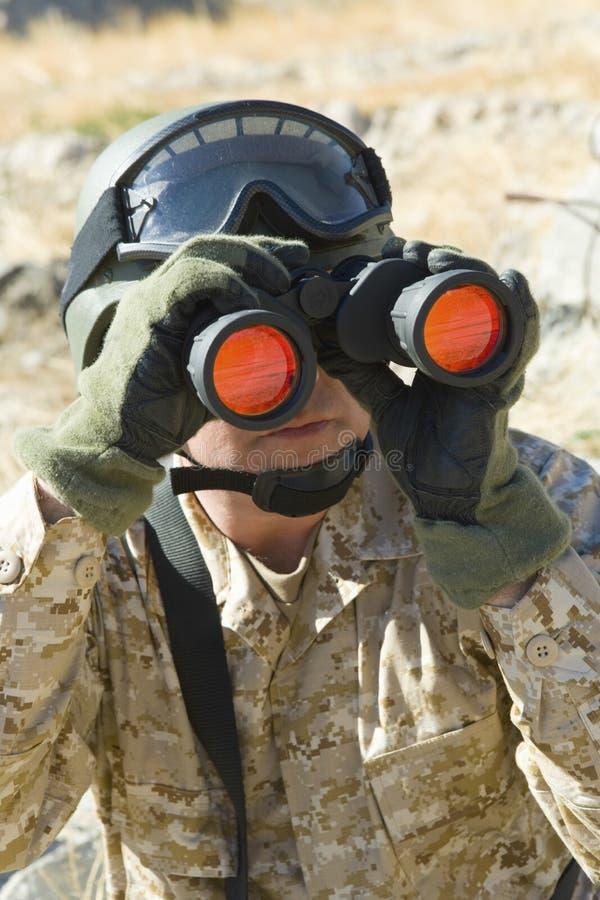 Soldado Looking Through Binoculars ao patrulhar fotos de stock royalty free